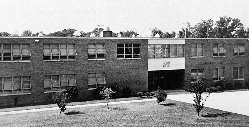 Black and white yearbook photograph of Washington Mill Elementary School taken in 1972. The trees and shrubs on the school grounds are still quite small. The classroom windows on both floors of the building are propped open.