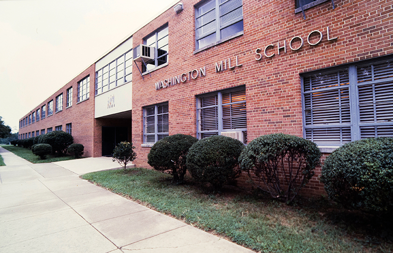 Color photograph of Washington Mill Elementary School's main entrance taken between 1983 and 1988. The windows are closed and two rooms have window-mounted air conditioning units installed.