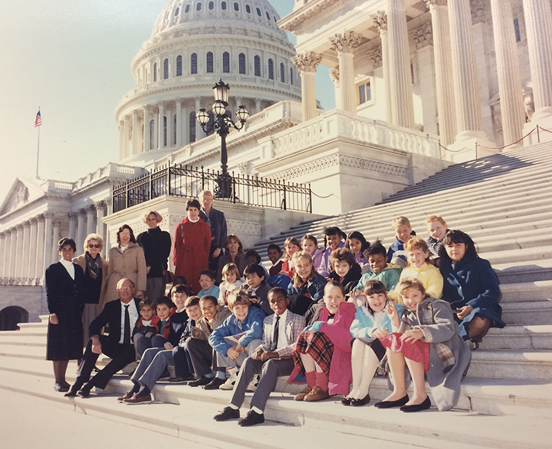 Color photograph of Washington Mill students on a field trip to Washington, D.C. There are approximately 27 students seated on the steps of the U.S. Capitol building. Eight unidentified adults are pictured with them.