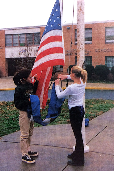 Color photograph from our 1997 to 1998 yearbook showing two students raising the American and Virginia flags on the pole in front of our school.