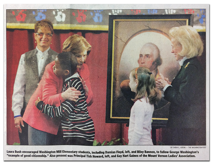Newspaper photograph of First Lady Laura Bush hugging a student with the portrait of George Washington in the background. Behind her, on the left, is Principal Tish Howard. Another student and a representative from the Mount Vernon Ladies' Association are to the right of Bush. The image caption reads: Laura Bush encouraged Washington Mill Elementary students, including Damian Floyd, left, and Riley Bannon, to follow George Washington's example of good citizenship. Also present was Principal Tish Howard, left, and Gay Hart Gaines of the Mount Vernon Ladies' Association.
