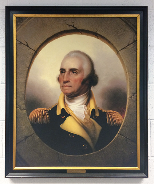Photograph of the Washington portrait on the wall in our library. It is a portrait of Washington in later life when he was President of the United States. He is wearing a gold and black or dark blue uniform with gold epaulettes. There is a gray oval matte around Washington and the picture is hung in a black and gold bordered frame.